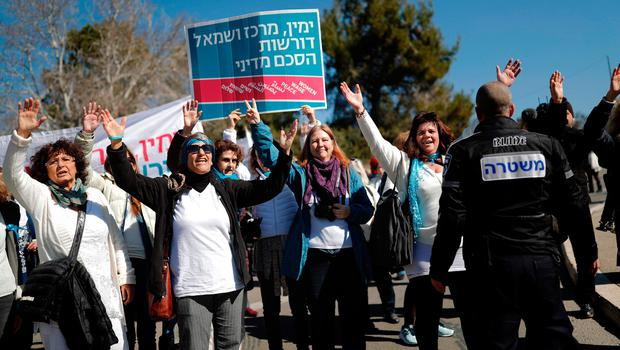 Israeli left wing activists from the Peace Now movement protest outside  the Knesset (Parliament) on January 30, 2017, to protest in support of the evicition of those living in the settlement outpost of Amona, which was established in 1997 and built on private Palestinian land.  Israel's parliament began discussions on the final adoption of a bill retroactively legalising thousands of homes on private Palestinian land in the occupied West Bank. / AFP PHOTO / THOMAS COEXTHOMAS COEX/AFP/Getty Images