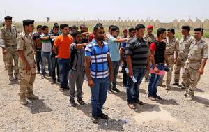 Men line up outside the main army recruiting centre in Baghdad yesterday to volunteer