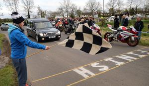 PACEMAKER, BELFAST, 27/4/2017: Chequered flags are waved as the hearse carrying the coffin of Italian rider Dario Cecconi crosses the finish line during the lap of honour of the Tandragee 100 circuit in Co Armagh in his memory following his death in a crash at last Saturday's races. PICTURE BY STEPHEN DAVISON
