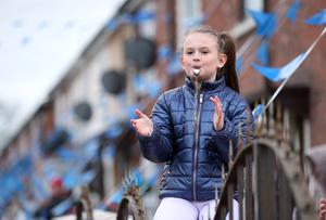 A young girl from the Whiterock Gardens area of Belfast blows a whistle and applauds the NHS and key workers. Pic Stephen Davison