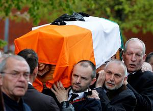 """Bobby Storey (right) and Sean 'Spike' Murray (centre) carry the coffin of Gerard """"Jock"""" Davison, a former IRA commander, in the Market's area of Belfast."""