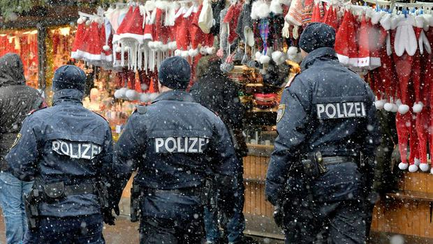 """TOPSHOT - Policemen patrol over the """"Wiener Christkindlmarkt"""" Christmas market in Vienna on December 20, 2016, as security measures are taken after a deadly rampage by a lorry driver at a Berlin Christmas market. Twelve people were killed in the assault at the Berlin shopping district popular with tourists, and 48 people injured, including 18 who are severely wounded. / AFP PHOTO / APA / HERBERT PFARRHOFER / Austria OUTHERBERT PFARRHOFER/AFP/Getty Images"""