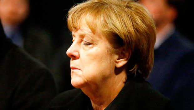 """TOPSHOT - German Chancellor Angela Merkel reacts before signing the book of condolences on December 20, 2016 inside the Kaiser-Wilhelm-Gedaechtniskirche (Kaiser Wilhelm Memorial Church), the day after an attack at the nearby Christmas market in central Berlin.  German police said they were treating as """"a probable terrorist attack"""" the killing of 12 people when the speeding lorry cut a bloody swath through the packed Berlin Christmas market. / AFP PHOTO / POOL / HANNIBAL HANSCHKEHANNIBAL HANSCHKE/AFP/Getty Images"""