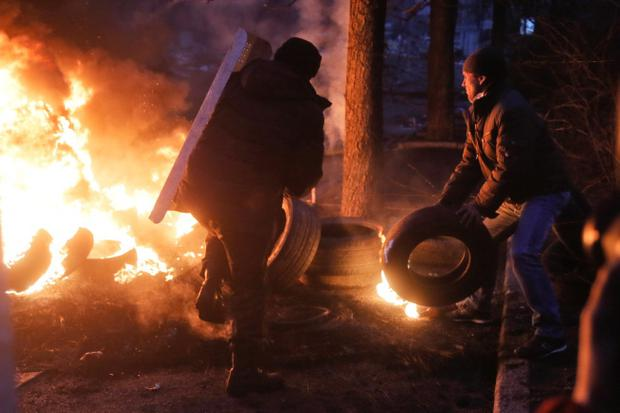 Activists burn tyres at barricades close to Independence Square, the epicenter of the country's current unrest, in Kiev, Ukraine, Thursday, Feb. 20, 2014, as, according to the protesters, the resulting heavy black smoke does not  allow riot police snipers to aim easily at protesters. Fierce clashes between police and protesters in Ukraine's capital have shattered the brief truce Thursday and an Associated Press reporter has seen dozens of bodies laid out on the edge of the protest encampment. (AP Photo / Efrem Lukatsky)