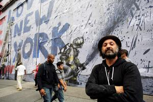 """Street artist Thierry Guetta poses for a portrait in front of the mural """"9/11"""" that he installed on the facade of the Century 21 department store, Wednesday, Sept 10, 2014, in New York. The installation, which will last three weeks, is an homage to New Yorkers who endured the terror attacks of Sept. 11, 2001, according to the Los Angeles-based artist who goes by the name, """"Mr. Brainwash."""" The store faces the World Trade Center where the 9/11 anniversary ceremony will be held Thursday. (AP Photo/Mark Lennihan)"""