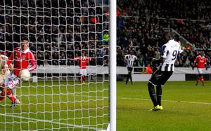 NEWCASTLE, ENGLAND - APRIL 11: Papiss Demba Cisse of Newcastle scores their first goal during the UEFA Europa League quarter final second leg match between Newcastle United and SL Benfica at St James' Park on April 11, 2013 in Newcastle upon Tyne, England. (Photo by Paul Thomas/Getty Images)