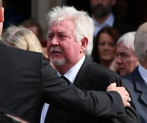 Musician Colum Arbuckle is comforted during the funeral of BBC broadcaster Gerry Anderson at St Eugene's Cathedral in Londonderry. PRESS ASSOCIATION Photo. Picture date: Sunday August 24, 2014. See PA story FUNERAL Anderson. Photo credit should read: Niall Carson/PA Wire