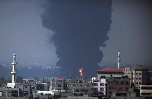 Seen from Gaza City, smoke and flames rise from Gaza's electricity distribution company plant after it was hit by Israeli strikes in the Nusseirat refugee camp, central Gaza Strip,Tuesday, July 29, 2014. Hours after Gaza's only power plant was hit, a tall column of thick black smoke continued to rise from a burning fuel tank there. The plants shutdown was bound to lead to further serious disruptions of the flow of electricity and water to Gazas 1.7 million people. (AP Photo/Lefteris Pitarakis)