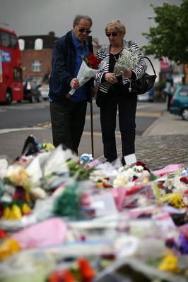 LONDON, ENGLAND - MAY 23:  Members of the community lay flowers outside Woolwich Barracks on May 23, 2013 in London, England. A British soldier was murdered by suspected Islamists near London's Woolwich Army Barracks yesterday in a savage knife attack. British Prime Minister David Cameron has said that the 'appalling' attack appeared to be terror related. (Photo by Dan Kitwood/Getty Images)