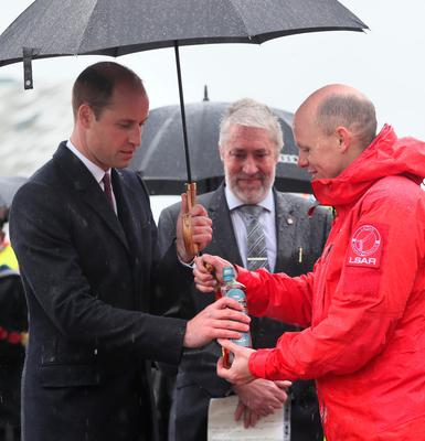 The Duke of Cambridge (left) receives a bottle of Bushmills Whisky to name a life boat for Lagan Search and Rescue, a rescue and lifeboat service that covers the Belfast Harbour Estate, River Lagan and the estuarial waters of Belfast Lough, in the Titanic Quarter, as part of his tour of Belfast. PRESS ASSOCIATION Photo. Picture date: Wednesday October 4, 2017. Brian Lawless/PA Wire