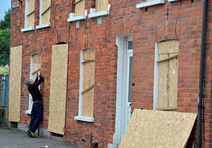 A resident of Chobham street boards up his windows to protect his home from the bonfire built nearby as people make final preparations for the Eleventh Night bonfire.  (Photo by Charles McQuillan/Getty Images)
