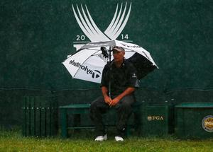 LOUISVILLE, KY - AUGUST 08:  David Hearn's caddie Brent Everson waits under an umbrella on the first tee during the weather-delayed second round of the 96th PGA Championship at Valhalla Golf Club on August 8, 2014 in Louisville, Kentucky.  (Photo by Sam Greenwood/Getty Images)