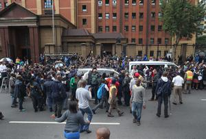 Media and public surround the car carrying Oscar Pistorius as he leaves the North Gauteng High Court after the second day of his trial accused of the murder of his girlfriend Reeva Steenkamp on March 4, 2014 in Pretoria, South Africa. (Photo by Christopher Furlong/Getty Images)