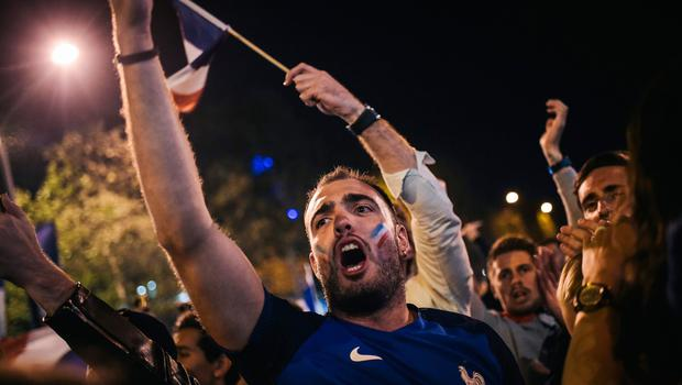 People celebrate France's victory on the Champs Elysees in Paris on July 10, 2018, after the final whistle of the Russia 2018 World Cup semi-final football match between France and Belgium. / AFP PHOTO / Lucas BARIOULETLUCAS BARIOULET/AFP/Getty Images