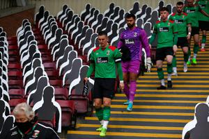 MOTHERWELL, SCOTLAND - AUGUST 27: Marcus Kane of Glentoran leads out his team through the empty stands next to the cardboard cut outs of fans during the UEFA Europa League qualification match between Motherwell and Glentoran  at Fir Park on August 27, 2020 in Motherwell, Scotland. (Photo by Ian MacNicol/Getty Images)
