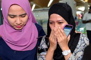 Relatives of passengers aboard the Malaysia Airlines Flight 17 react as they arrive at Kuala Lumpur International Airport in Sepang, Malaysia, Friday, July 18, 2014. The Malaysia Airlines jetliner that went down in war-torn Ukraine did not make any distress call, Malaysia's prime minister said Friday, adding that its flight route had been declared safe by the global civil aviation body. (AP Photo)