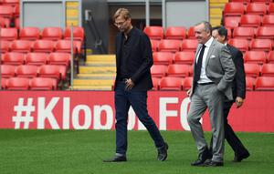 "Liverpool's new German manager Jurgen Klopp (L) walks on the pitch with Liverpool's chairman Tom Werner (R obscured) and managing director Ian Ayre (C) after a press conference to announce his new appointment at Anfield in Liverpool, northwest England, on October 9, 2015. Klopp described his job as ""the biggest challenge"" in world football on October 9 following his appointment as the successor to Brendan Rodgers. Former Borussia Dortmund head coach Klopp, 48, was appointed on October 8 on a three-year contract following the dismissal of Rodgers, who was sacked October 4 after three and a half years at the club.  AFP PHOTO / PAUL ELLIS    RESTRICTED TO EDITORIAL USE. No use with unauthorized audio, video, data, fixture lists, club/league logos or 'live' services. Online in-match use limited to 75 images, no video emulation. No use in betting, games or single club/league/player publications.PAUL ELLIS/AFP/Getty Images"