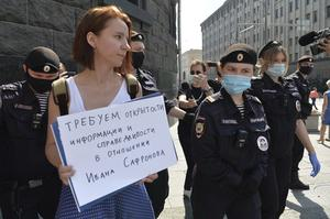 Police officers detain Yelena Chernenko, a Kommersant journalist who worked with Ivan Safronov (AP/Denis Kaminev)