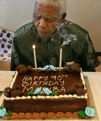 JOHANNESBURG, SOUTH AFRICA - AUGUST 5: In this handout from Nelson Mandela Foundation, former South African president and Nobel peace prize laureate Nelson Mandela blows out the candles on his birthday cake received from the staff in honour his 90th birthday, at the Nelson Mandela Foundation August 5, 2008  in Houghton, Johannesburg (Photo by Juda Ngwenya/Nelson Mandela Foundation via Getty Images) *** Local Caption *** Nelson Mandela