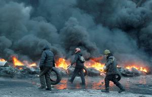 Protesters throw tires onto a fire during a clash with police in central Kiev, Ukraine, Thursday, Jan. 23, 2014. Thick black smoke from burning tires engulfed parts of downtown Kiev as an ultimatum issued by the opposition to the president to call early elections or face street rage was set to expire with no sign of a compromise on Thursday.    (AP Photo/Efrem Lukatsky)
