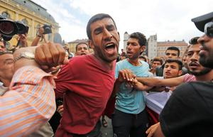 Migrants push and shout as they gather in front of the railway station in Budapest, Hungary, Thursday, Sept. 3, 2015. Over 150,000 migrants have reached Hungary this year, most coming through the southern border with Serbia, and many apply for asylum but quickly try to leave for richer EU countries.(AP Photo/Frank Augstein)