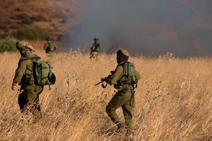 Israeli soldiers inspect a field where rockets fired from Syria landed near Kfar Szold, causing fires but no injuries, in northern Israel, close to the Golan Heights and the border with Lebanon, on August 20, 2015. AFP/Getty Images