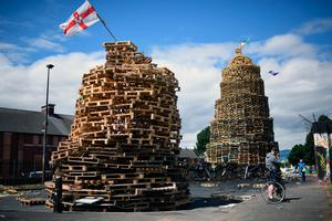 BELFAST, NORTHERN IRELAND - JULY 11:  Loyalists finish a bonfire in East Belfast in preparation for the 11th night celebrations on July 11, 2017 in Belfast, Northern Ireland. Tradition holds that the bonfires commemorate the lighting of fires on the hills to help Williamite ships navigate through Belfast Lough at night when Protestant King William III and his forces landed at Carrickfergus to fight the Catholic Jacobites, supporters of the exiled Catholic King James II. The bonfires also mark the beginning of the annual 12th of July Orange parades.  (Photo by Jeff J Mitchell/Getty Images)
