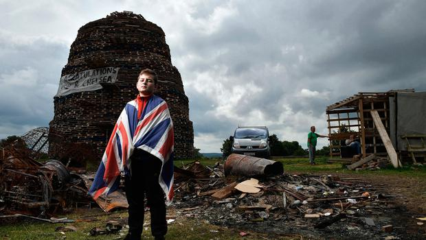 LISBURN, NORTHERN IRELAND - JULY 10: Having finished school for the summer 13 year old Tyler Reid helps guard the Lisburn bonfire on July 10, 2017 in Lisburn, Northern Ireland. The bonfires, which are lit on the stroke of midnight on the 11th night, mark the beginning of the annual 12th of July Orange parades in Northern Ireland. The annual Orange marches celebrate the protestant King William of Orange's victory over the catholic English King James II at the Battle of the Boyne in 1690. (Photo by Charles McQuillan/Getty Images) *** BESTPIX ***