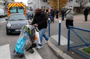 A man pulls a stroller near a pre-school after a masked assailant with a box-cutter and scissors who mentioned the Islamic State group attacked a teacher, Monday, Dec.14, 2015 in Paris suburb Aubervilliers. The assailant remains at large, and the motive for the attack in the town of Aubervilliers is unclear, authorities said. (AP Photo/Michel Euler)