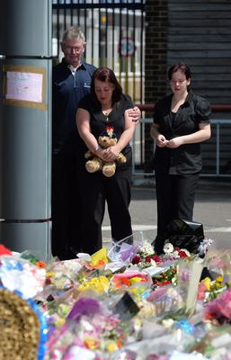 Lyn Rigby, mother of Drummer Lee Rigby, holding a teddy bear joins other family members as they look at floral tributes outside Woolwich Barracks as they visited the scene of his murder in Woolwich, south-east London. PRESS ASSOCIATION Photo. Picture date: Sunday May 26, 2013. They laid flowers at the Woolwich Barracks where the 25-year-old soldier with the Royal Regiment of Fusiliers was based, and where hundreds of floral tributes have already been left by wellwishers.  See PA story POLICE Woolwich. Photo credit should read: John Stillwell/PA Wire