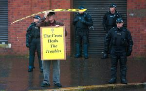 Picture - Kevin Scott / Presseye  Belfast - Northern Ireland - Monday 13th July 2015 -  Ardoyne Parade Outward   Pictured is a protester sheltering from the rain at the Orange order parade and its associated protests as it makes its way past the flashpoint of the Ardoyne Shopfront in Belfast, Northern Ireland.    Picture by Kevin Scott  / Presseye.