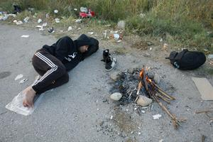 "This handout photograph taken and released by Caritas Internationalis on September 5, 2015 in Idomeni, northern Greece, shows a migrant sleeping on the road as he waits to be allowed to cross the Greek-Macedonian border. More than 230,000 refugees and migrants have arrived in Greece by sea this year, a huge rise from 17,500 in the same period in 2014, shipping ministry said on September 3. AFP PHOTO / CARITAS INTERNATIONALIS / MATTHIEU ALEXANDRE  -- EDITORS NOTE -- RESTRICTED TO EDITORIAL USE - MANDATORY CREDIT ""AFP PHOTO/ MATTHIEU ALEXANDRE/CARITAS INTERNATIONALIS"" - NO MARKETING NO ADVERTISING CAMPAIGNS ----CAR04MATTHIEU ALEXANDRE/AFP/Getty Images"