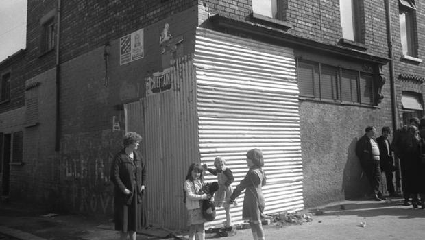 The people standing around this boarded-up bar in West Belfast told me that the night before a British Army armoured car had driven through the corner doorway, demolishing it.