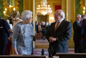 WINDSOR, ENGLAND - APRIL 08:  Queen Elizabeth II (L) shows Irish President Michael D Higgins (R) Irish related items from the Royal Collection, in the Green Drawing Room at Windsor Castle on April 8, 2014 in Windsor, England. This is the first official visit by the head of state of the Irish Republic to the United Kingdom.  (Photo by Justin Tallis - WPA Pool/Getty Images)