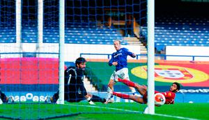 Let off: Everton's Tom Davies (centre) sees his shot hit the post