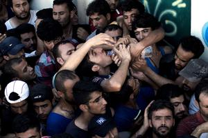 A migrant drinks water as he waits with hundreds of others to complete a registration procedure by the police at a stadium on the Greek island of Kos on August 12, 2015. Tensions on the tourist island are high with its mayor claiming there were 7,000 migrants stranded on Kos, which has a population of only 30,000 people. A Kos police officer was suspended on August 10 after being filmed slapping and shoving migrants queueing outside the local police station as they waited to be documented so they could go on to Athens. The UN refugee agency's division for Europe said 124,000 refugees and migrants have landed in Greece since the beginning of the year. AFP PHOTO / ANGELOS TZORTZINISANGELOS TZORTZINIS/AFP/Getty Images
