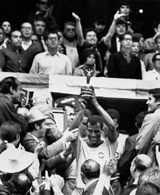 (FILES) This file photo taken on June 21, 1970 shows Brazilian national soccer team captain and defender Carlos Alberto smiling as he holds aloft the Jules Rimet Cup after Brazil defeated Italy 4-1 in the World Cup final in Mexico City.  Carlos Alberto, captain of the great Brazil team that won the 1970 World Cup, died on Tuesday of a heart attack in Rio at the age of 72, Brazil's Sportv, for whom he worked, announced.  / AFP PHOTO / STAFFSTAFF/AFP/Getty Images