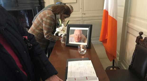 Members of the public sign a book of condolence for the late Irish broadcaster Gay Byrne at the Mansion House in Dublin.
