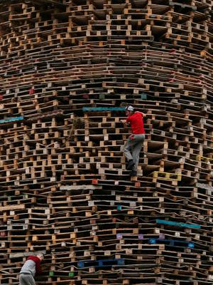 Youths climb a bonfire in the New Mosley area of Belfast. Niall Carson/PA Wire.