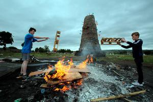 Local youths burn palets next to the New Mossley bonfire, one of the largest in the province is seen on the outskirts of Belfast. AFP PHOTO / PAUL FAITHPAUL FAITH/AFP/Getty Images.