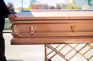A funeral director transports the body of an Irish student who died Tuesday when a Berkeley apartment balcony collapsed,  Friday, June 19, 2015, in Oakland Calif. Caskets bearing four of the six victims arrived at St. Columba Catholic Church for a vigil Friday afternoon. (AP Photo/Noah Berger)