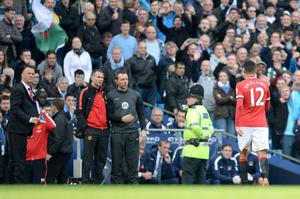 Manchester United's Chris Smalling (right) leaves the pitch after being sent-off as Manchester United manager Louis van Gaal (left) and assistant manager Ryan Giggs (centre) look on during the Barclays Premier League match at the Etihad Stadium, Manchester. Martin Rickett/PA Wire.