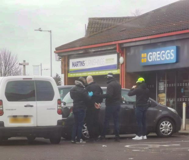 A man is arrested by armed security forces outside Greggs at the Twin Spires Centre, Northumberland Street off the Falls Road, Belfast.