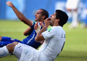 Luis Suarez of Uruguay and Giorgio Chiellini of Italy react after a clash during the 2014 FIFA World Cup Brazil Group D match between Italy and Uruguay at Estadio das Dunas on June 24, 2014 in Natal, Brazil.  (Photo by Matthias Hangst/Getty Images)