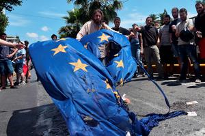 Leftist protesters try to burn a European Union flag in front of the European Commission offices in Athens on July 2, 2015.  Greece's Prime Minister Alexis Tsipras said on July 2 his country would remain united after the upcoming referendum, rejecting concerns the vote on bailout measures is splitting the country in two. AFP PHOTO/ LOUISA GOULIAMAKILOUISA GOULIAMAKI/AFP/Getty Images