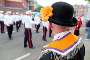 An Orangeman with an orange lily watches, as the main 12th July parade moves off from Carlisle circus in Belfast, on July 12, 2016. 12th July is the main marching day in the Orange Order calendar. The parades mark the 326th anniversary of King William III's victory at the Battle of the Boyne in 1690. / AFP PHOTO / PAUL FAITHPAUL FAITH/AFP/Getty Images