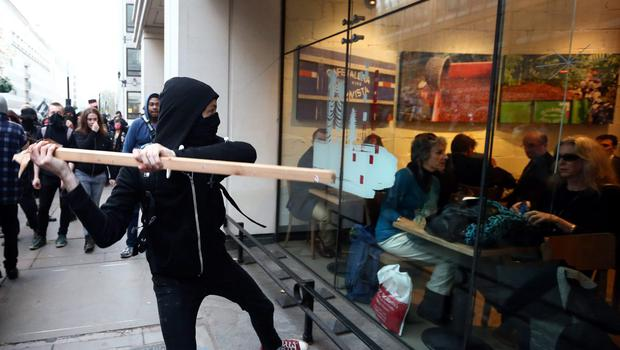A protester attempts to smash a Starbucks window during a demonstration against fees and cuts in the education system on November 19, 2014 in London, England. (Photo by Carl Court/Getty Images)