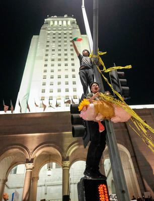 """Demonstrators climb a traffic light to protest a day after President-elect Donald Trump's victory, at a rally outside Los Angeles City Hall in Los Angeles, California, on November 9, 2016. Protesters burned a giant orange-haired head of Donald Trump in effigy, lit fires ins the streets and blocked traffic lanes late on November 9 as rage over the billionaire's election victory spilled onto the streets of US cities. From New York to Los Angeles, thousands of people in around 10 cities rallied against the president-elect a day after his stunning win, some carrying signs declaiming """"Not our President"""" and """"Love trumps hate."""" / AFP PHOTO / RINGO CHIURINGO CHIU/AFP/Getty Images"""