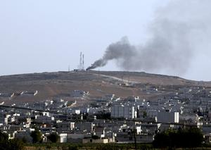 Smoke rises from the Syrian town of Kobani after an air strike, seen from near the Mursitpinar border crossing on the Turkish-Syrian border on October 7, 2014 near the southeastern town of Suruc in Sanliurfa province, Turkey. (Photo by Stringer/Getty Images)