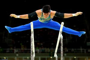 RIO DE JANEIRO, BRAZIL - AUGUST 08:  Sergio Sasaki of Brazil competes on the parallel bars during the men's team final on Day 3 of the Rio 2016 Olympic Games at the Rio Olympic Arena on August 8, 2016 in Rio de Janeiro, Brazil.  (Photo by Alex Livesey/Getty Images)